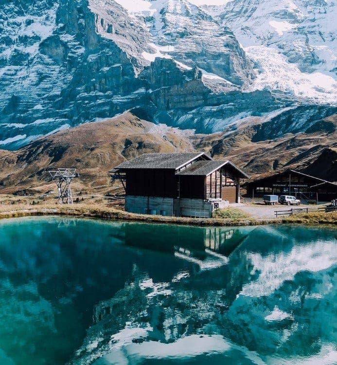 switzerland drone shot of a lake mountain cabin